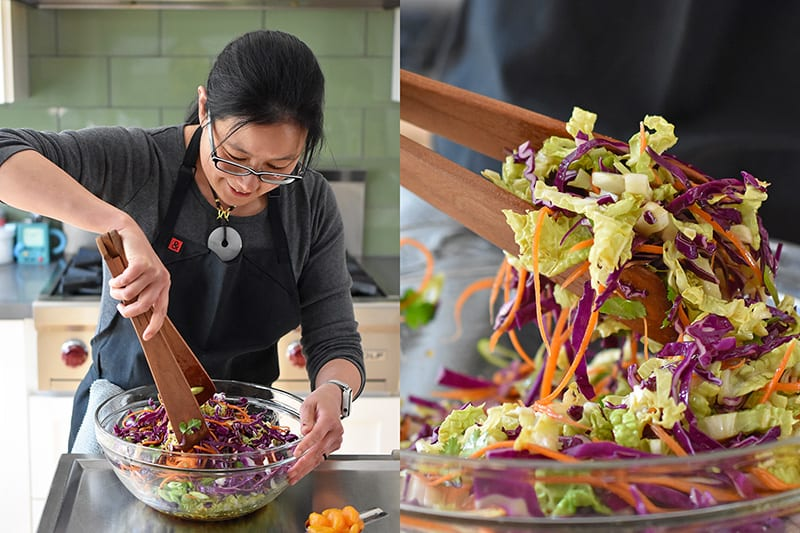 A woman is tossing Whole30-friendly Chinese Chicken Salad in a large clear bowl with wooden tongs.