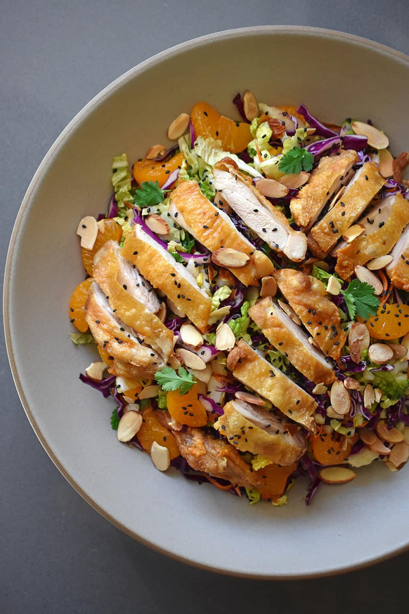 An overhead shot of Whole30-friendly Chinese Chicken Salad, a colorful blend of cabbage, carrots, mandarin oranges, herbs, and crispy Cracklin' Chicken.
