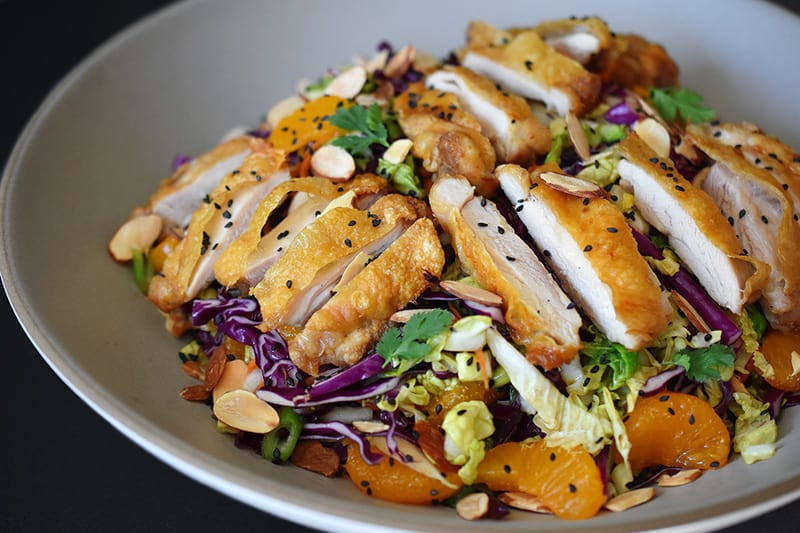 A close up of Whole30-friendly Chinese Chicken Salad, a colorful blend of cabbage, carrots, mandarin oranges, herbs, and crispy Cracklin' Chicken.
