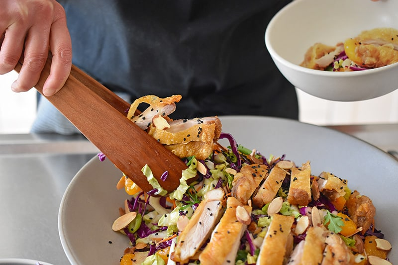 Using a pair of wooden tongs to transfer the paleo and Whole30-friendly Chinese Chicken Salad to a serving bowl. The best gluten-free Chinese Chicken Salad!