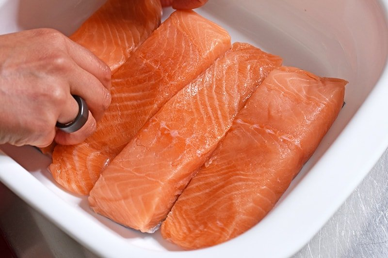 Four salmon fillets are placed in a snug fitting white dish with high sides.