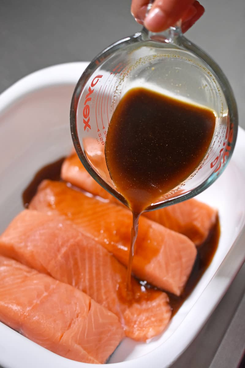 Pouring All-Purpose Stir-Fry Sauce over the salmon fillets to make Easy Teriyaki Salmon, a healthy Whole30 dinner.