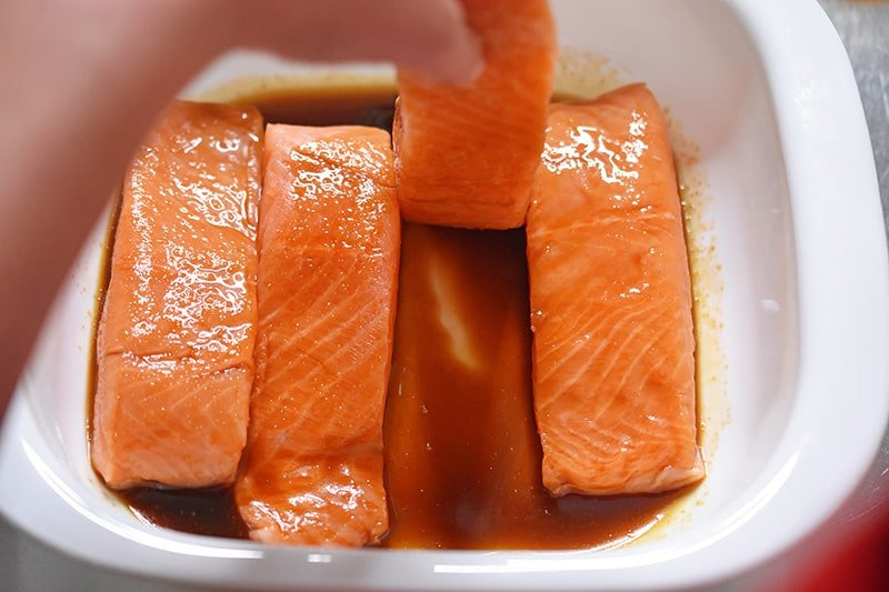 Someone is flipping the salmon fillets in the All-Purpose Stir-Fry Sauce to coat them.