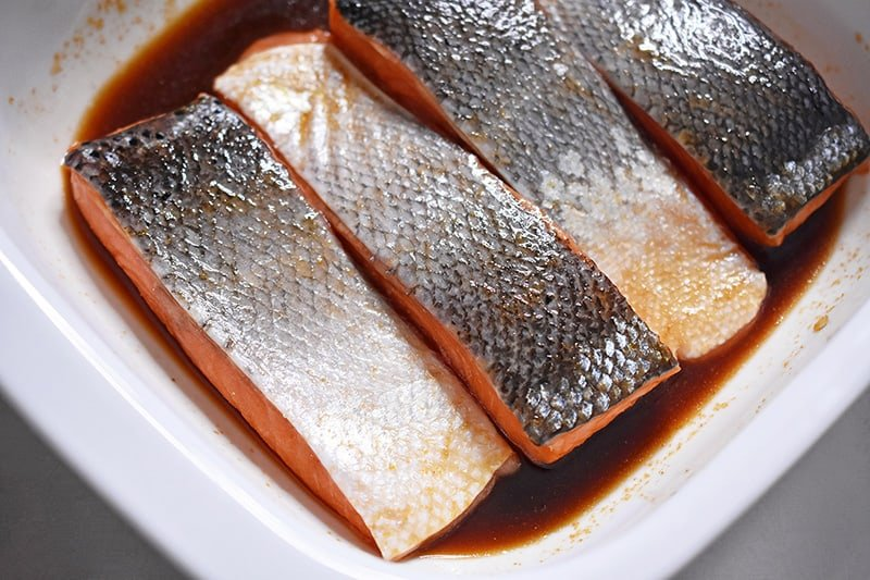 The salmon fillets are marinating skin-side up in the Whole30-friendly teriyaki sauce.