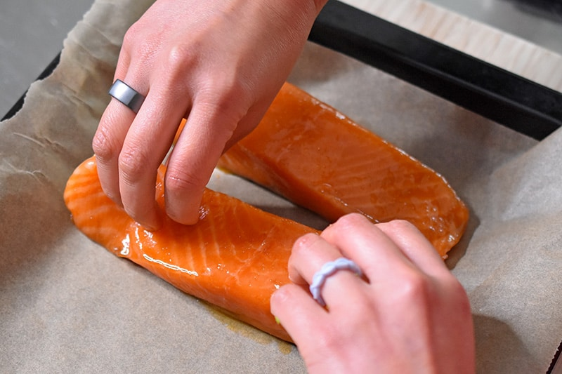 Two hands are placing the marinated teriyaki salmon skin-side down on a parchment paper lined baking sheet.