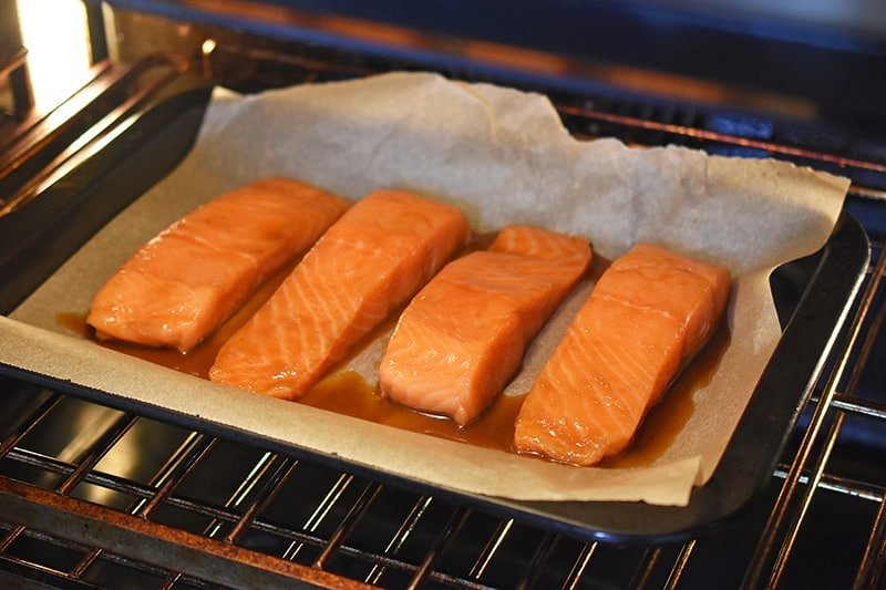 Four teriyaki salmon fillets are on a baking sheet in the oven.