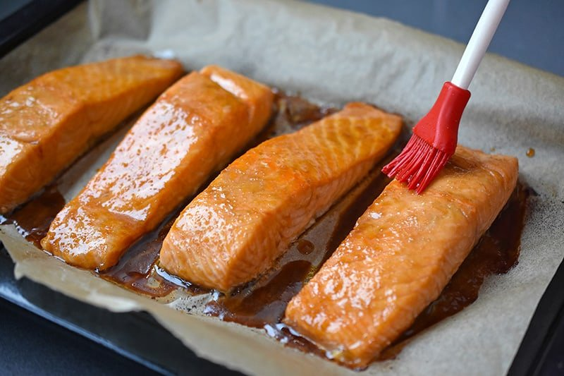 A brush is adding reserved All-Purpose Stir-Fry Sauce on the easy teriyaki salmon, a healthy Whole30 friendly dinner.