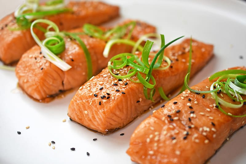 Easy gluten-free teriyaki salmon topped with scallions and toasted sesame seeds.