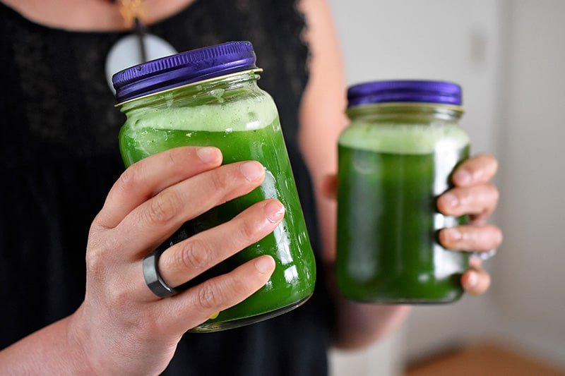 Two sealed mason jars filled with freshly shaken bright green cold brew matcha.