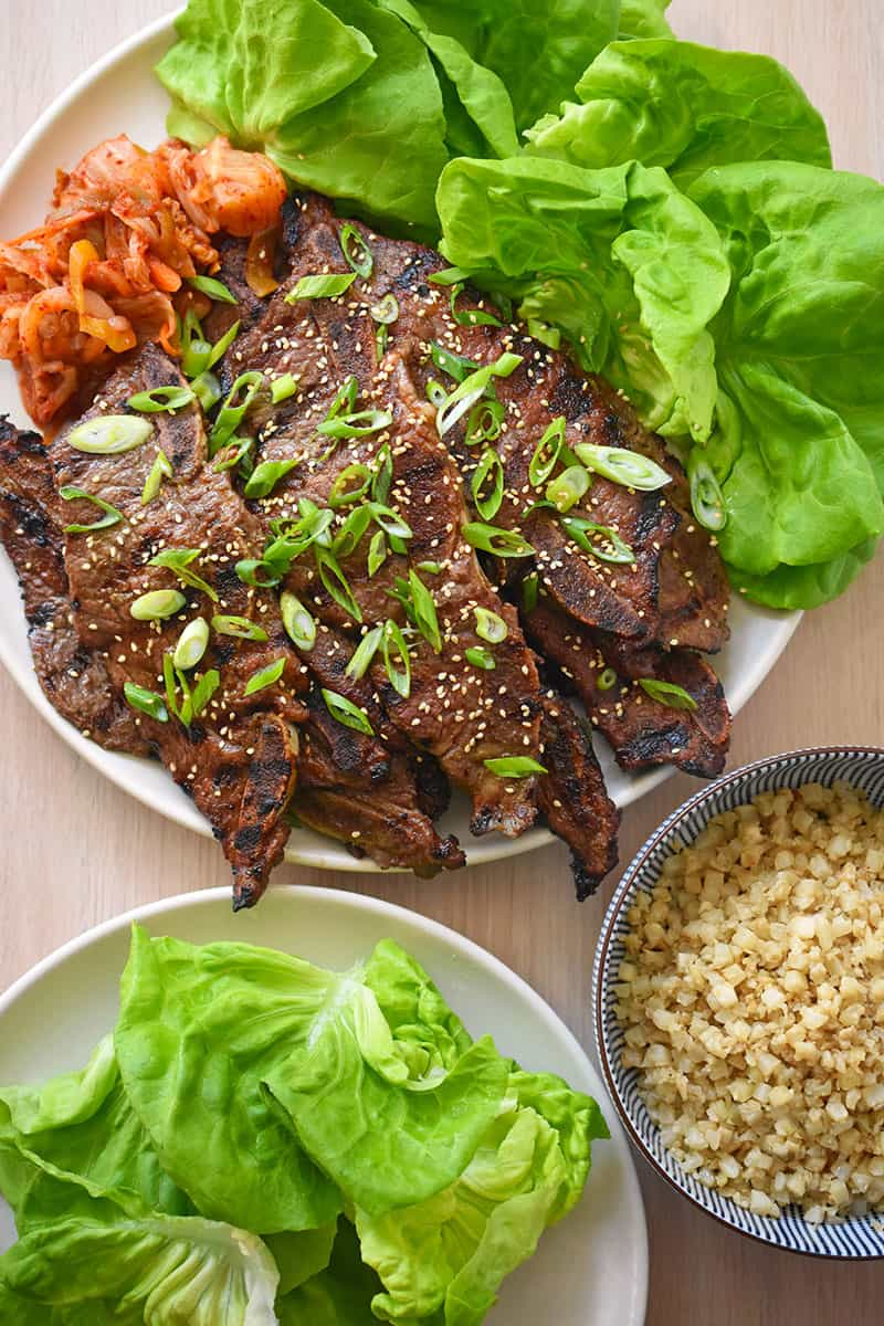 An overhead shot of a platter of Whole30 Kalbi or Galbi (Korean BBQ beef short ribs) served with lettuce leaves, cauliflower rice, and kimchi.