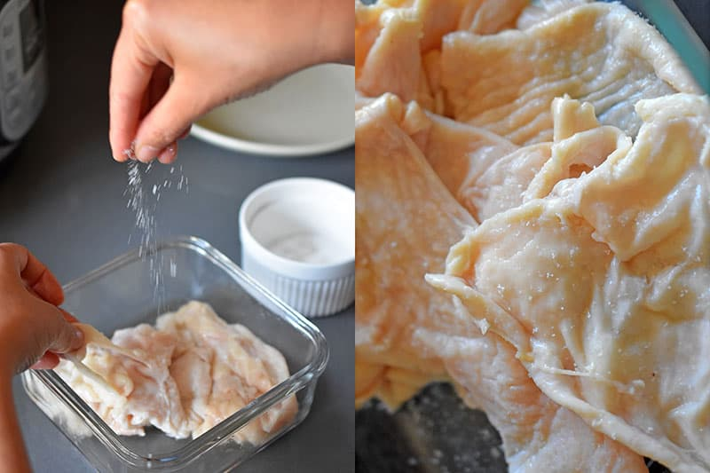 A hand is sprinkling salt on raw chicken skin.