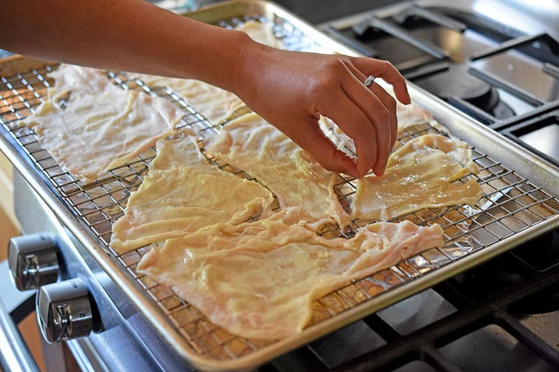 A hand placing raw chicken skins on a wire rack in a rimmed baking sheet to make oven-baked crispy chicken skins.