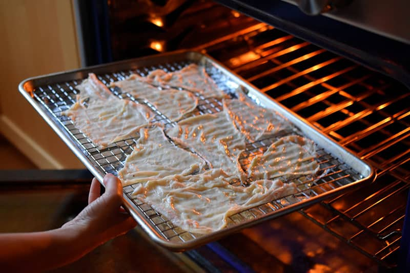 Placing a tray of chicken skins into the oven to make a keto snack.