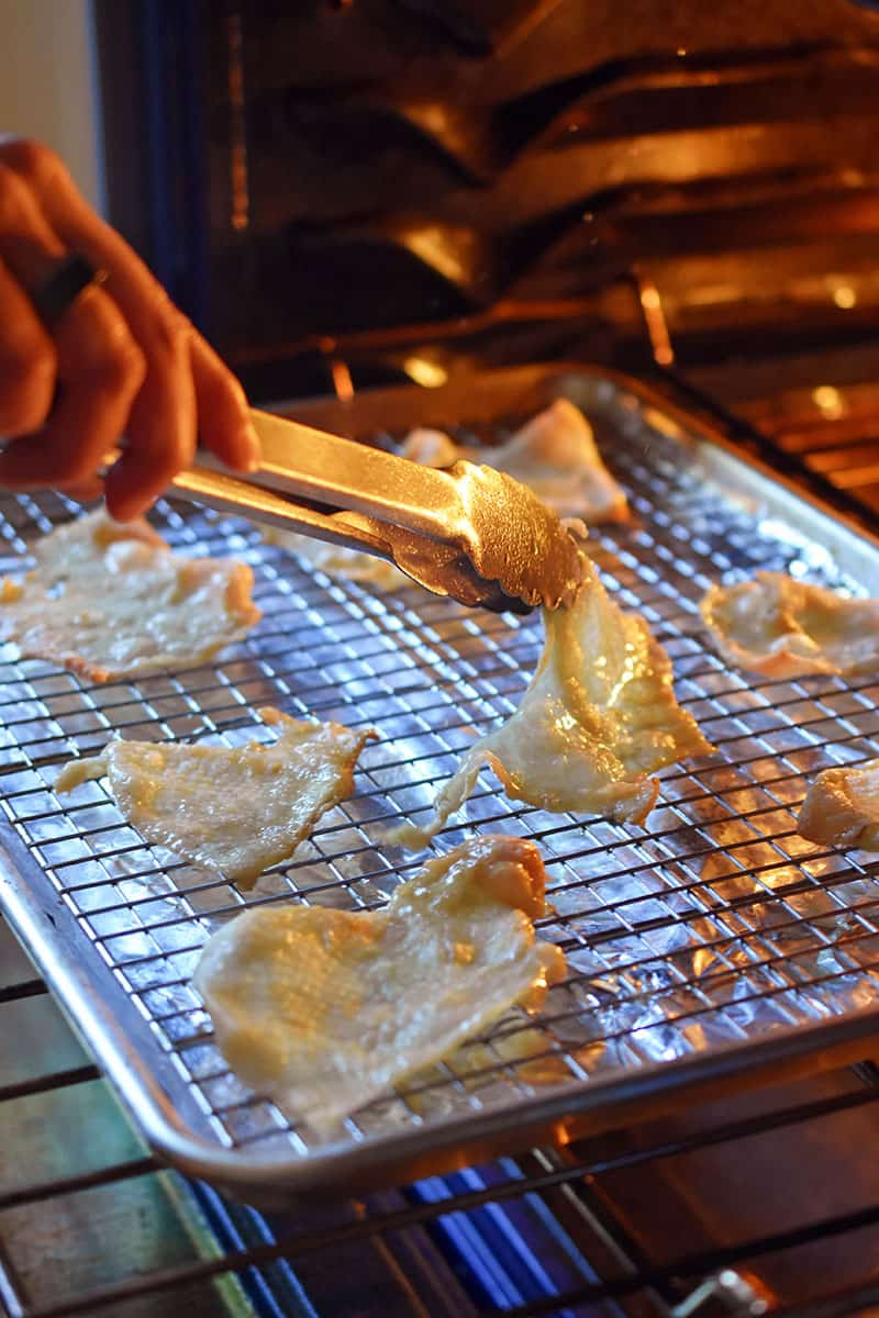 A person is using a pair of tongs to flip over chicken skins that are baking in the oven.
