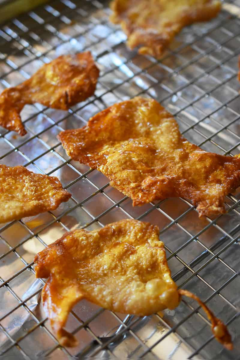 A tray of crispy chicken skin chips cooling on a wire rack.