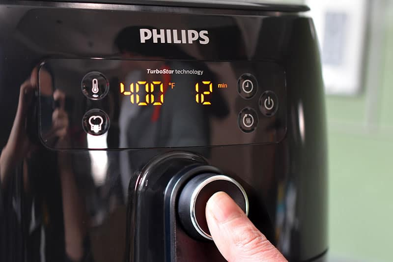 A person is programming an air fryer to cook at 400°F for 12 minutes