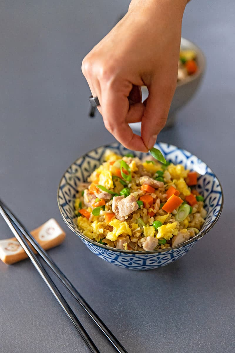 Someone adding scallions to a bowl filled with healthy cauliflower chicken fried rice.