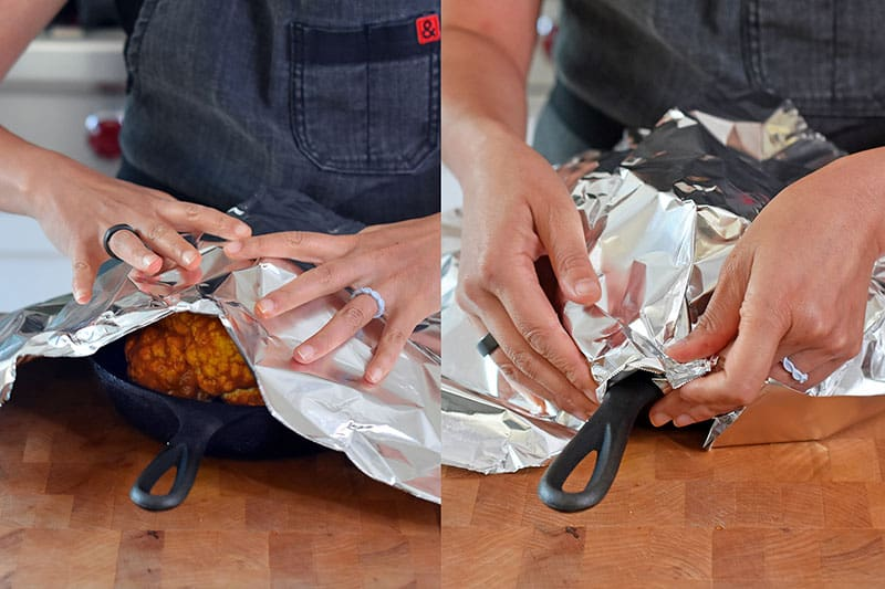 Someone covering Tandoori Whole Roasted Cauliflower with aluminum foil.