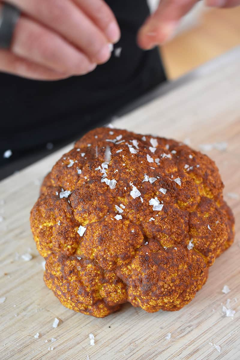 An overhead shot of someone sprinkling salt on top of Tandoori Whole Roasted Cauliflower