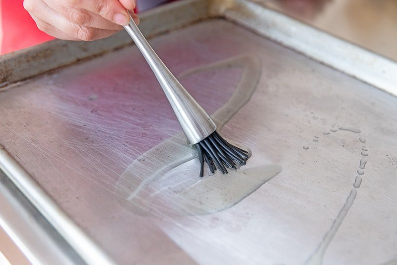 A silicone brush is spreading avocado oil on a rimmed baking sheet for a healthy sheet pan chicken dinner.