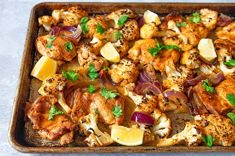 An overhead view of sheet pan Tandoori Chicken fresh from the oven with lemons and cilantro on top.