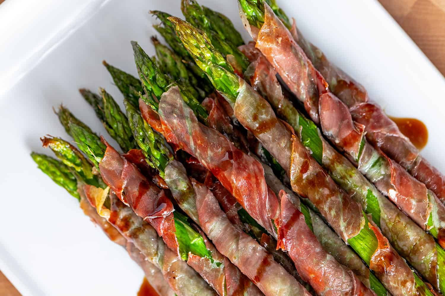 An overhead shot of a plate of Whole30 and paleo prosciutto wrapped asparagus drizzled with balsamic vinegar.