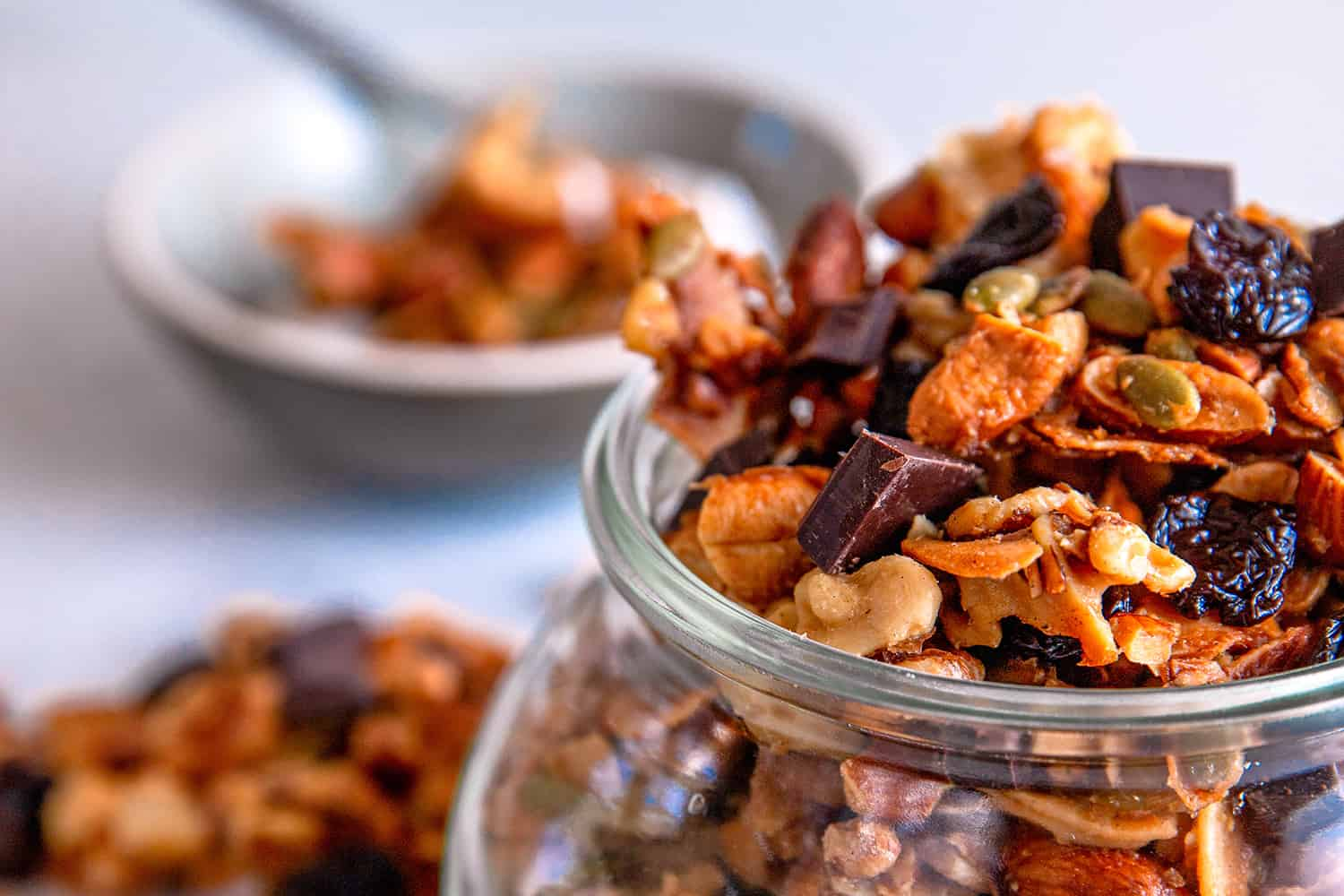 A close up of cherry chocolate paleo granola in a clear jar and a bowl of granola on top of coconut yogurt in the background.