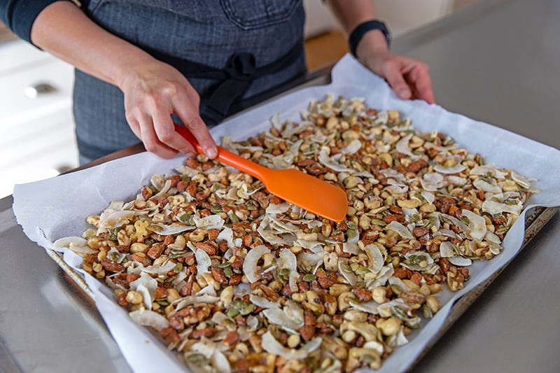 Someone is spreading the paleo granola into a single layer on a parchment-lined baking sheet with a red silicone spatula.