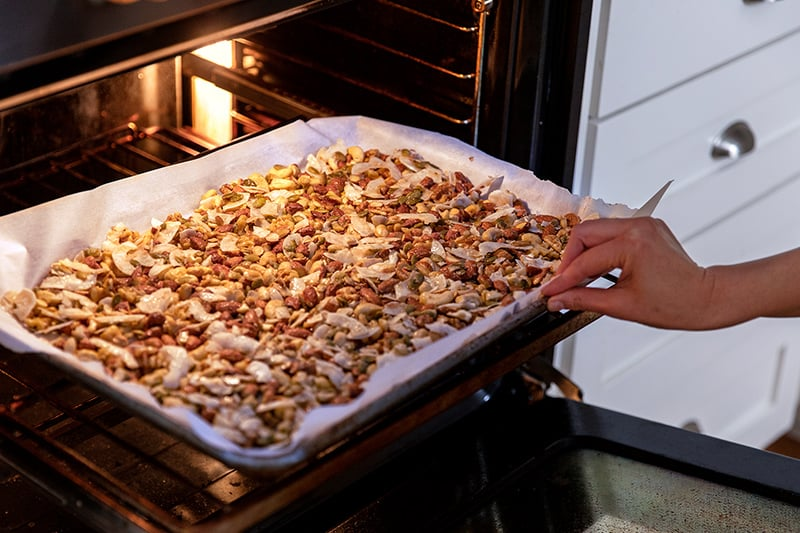 Placing the tray of chocolate cherry paleo granola into the oven.