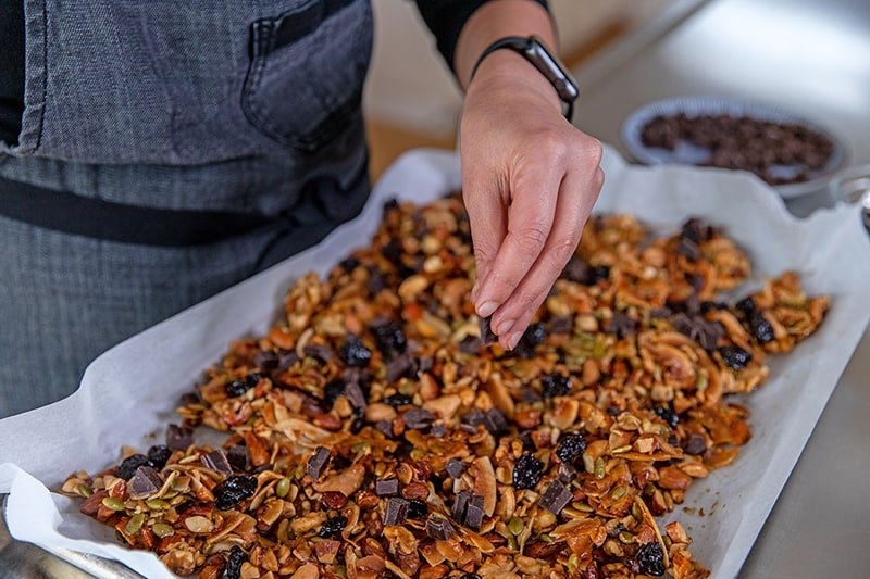 Someone adding dark chocolate chunks and dried cherries to cooled paleo granola on a rimmed baking sheet.