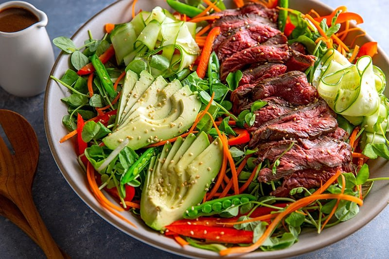 A side shot of a beautiful Whole30 Asian Steak Salad with a container of salad dressing on the side.