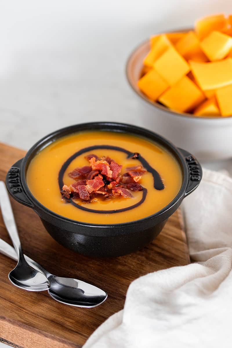 A black bowl filled with Instant Pot Butternut Squash Soup on a wooden cutting board.