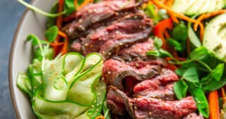 An overhead shot of Whole30 and Paleo Asian Steak Salad, a large white bowl topped with colorful vegetables and sliced seared flank steak.
