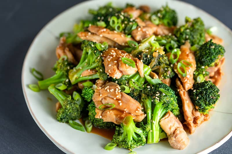 A closeup shot of chicken and broccoli stir-fry topped with toasted sesame seeds and sliced scallions.