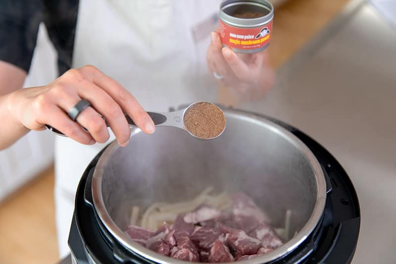 Adding a spoonful of Magic Mushroom Powder to an open Instant Pot filled with pork, onions, and garlic.
