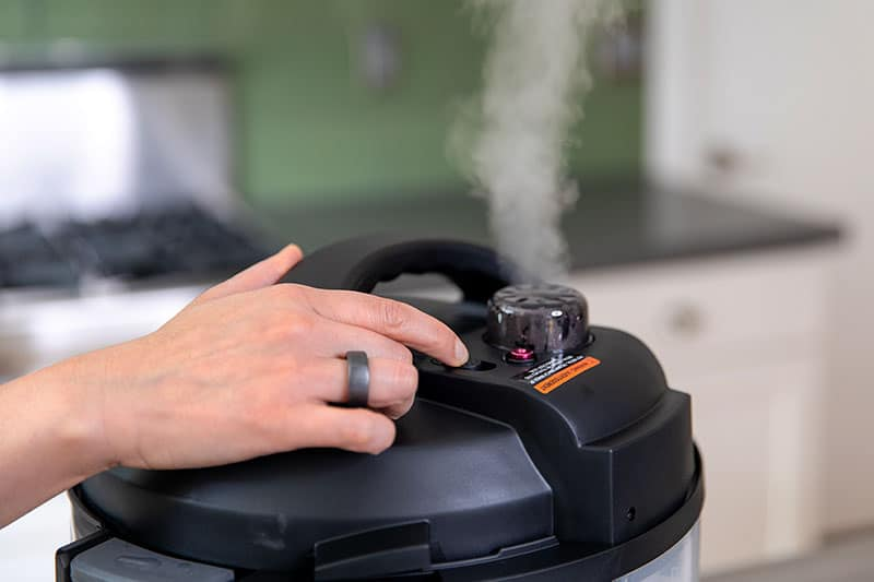 A hand is pressing the button to manually release the pressure on an Instant Pot Duo Evo Plus.