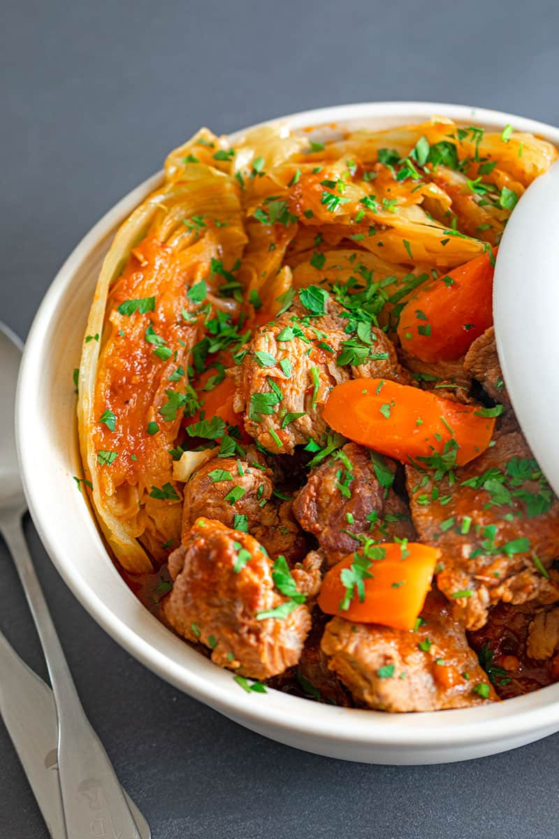 An overhead shot of a large bowl filled with Slow Cooker Pork and Cabbage stew, a paleo and Whole30-friendly healthy supper.