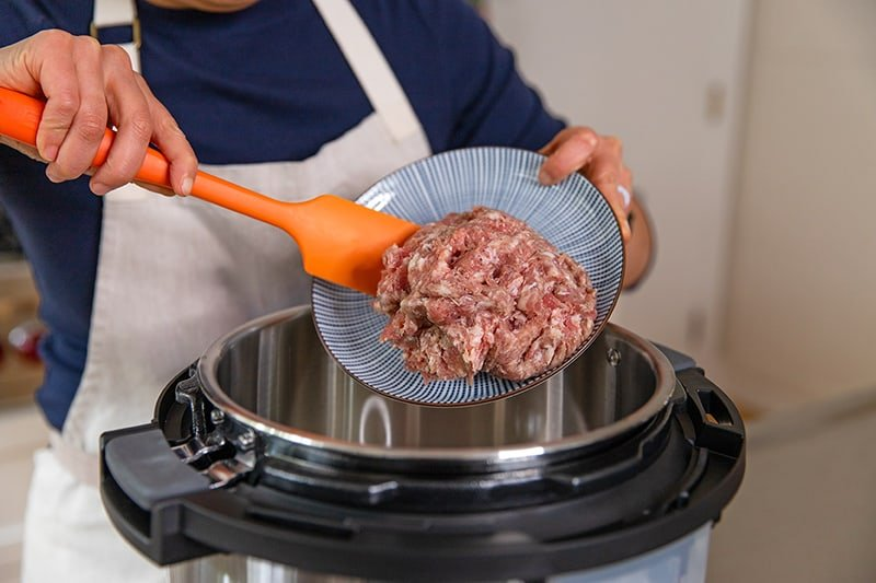 A person adding bulk Italian sausage to an open Instant Pot