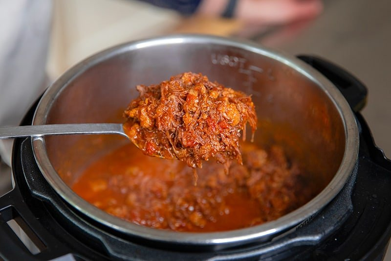 A metal serving spoon is scooping out a spoonful of easy Whole30 meat sauce from an open Instant Pot