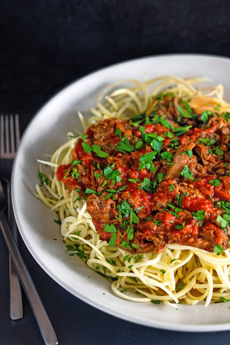 A large white bowl filled with spiralized sweet potato noodles topped with Whole30 Instant Pot Meat Sauce, an easy and healthy dinner.