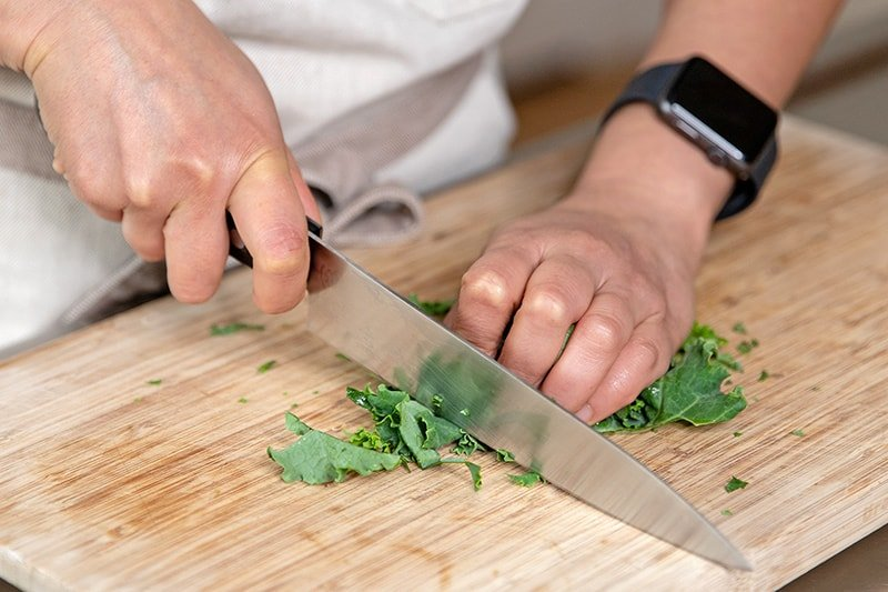 Slicing kale leaves into thin strips with a chef's knife on a wooden cutting board.