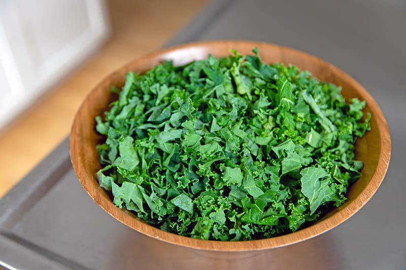 A large wooden bowl filled with sliced kale for a simple winter salad.