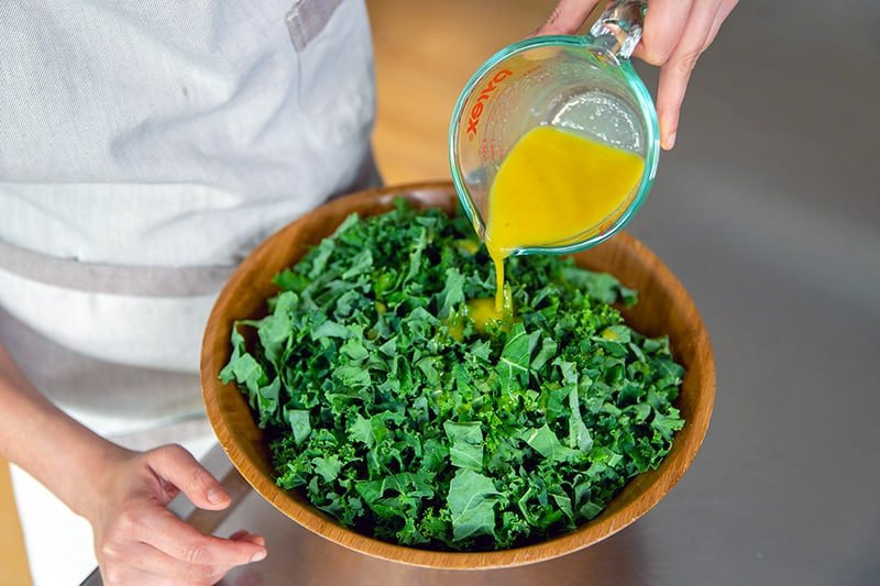 Pouring the lemon vinaigrette onto the sliced kale leaves in a big wooden bowl.