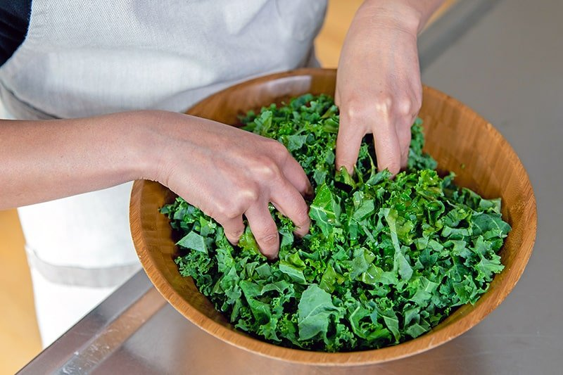 Two clean hands massaging the kale with the lemon vinaigrette.