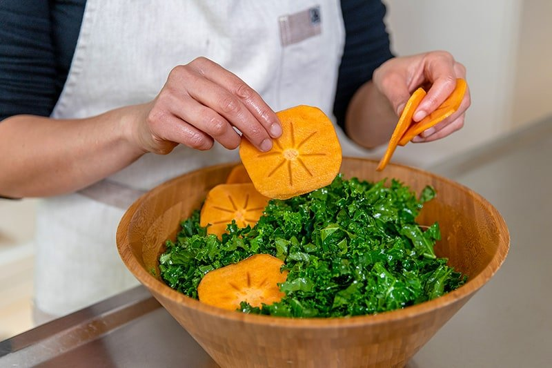 Adding thin slices of fuyu persimmons to a healthy kale salad dressed with a lemon vinaigrette