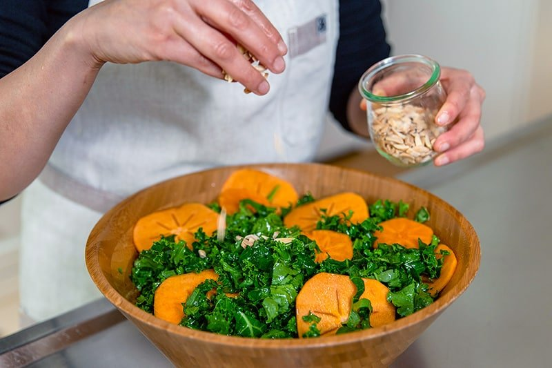 Sprinkling toasted almond slices on top of a kale salad with persimmons.