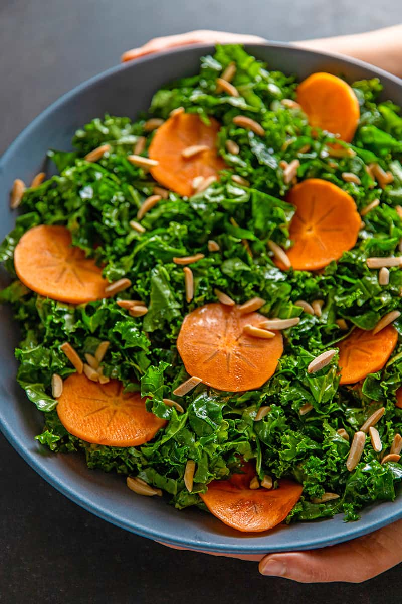 An overhead shot of two hands holding a large blue bowl filled with kale salad and persimmons and toasted almonds, a simple and delicious winter salad.