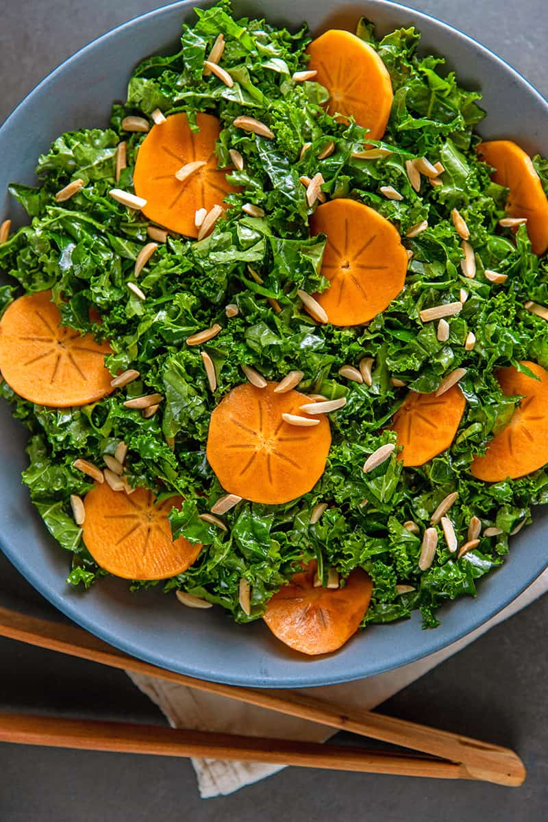 An overhead shot of a large blue bowl filled with Whole30 and vegan kale salad with persimmon next to a pair of wooden tongs.