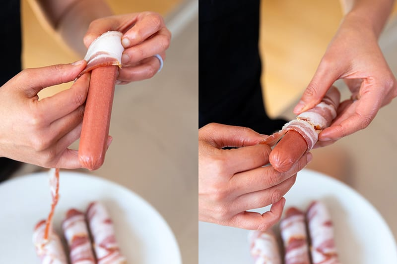 A person wrapping a piece of bacon around a hot dog in a single layer.