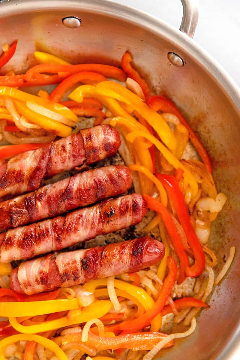 An overhead shot of paleo, keto, and Whole30 Sonoran hot dogs in a skillet with sliced onion and red and yellow bell peppers.
